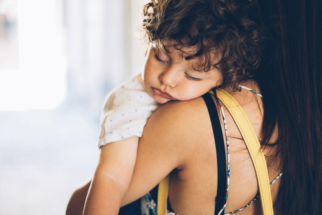 Kind schläft auf Schulter von Mama