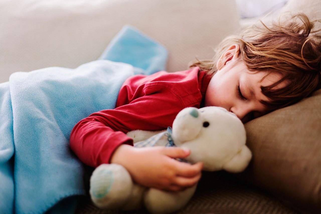 Kind schläft mit Bär