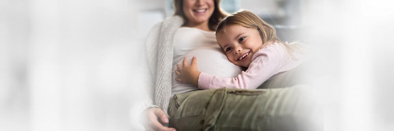 Kleines Kind hält den Bauch der schwangeren Mutter