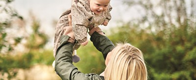 Mother holds baby in air