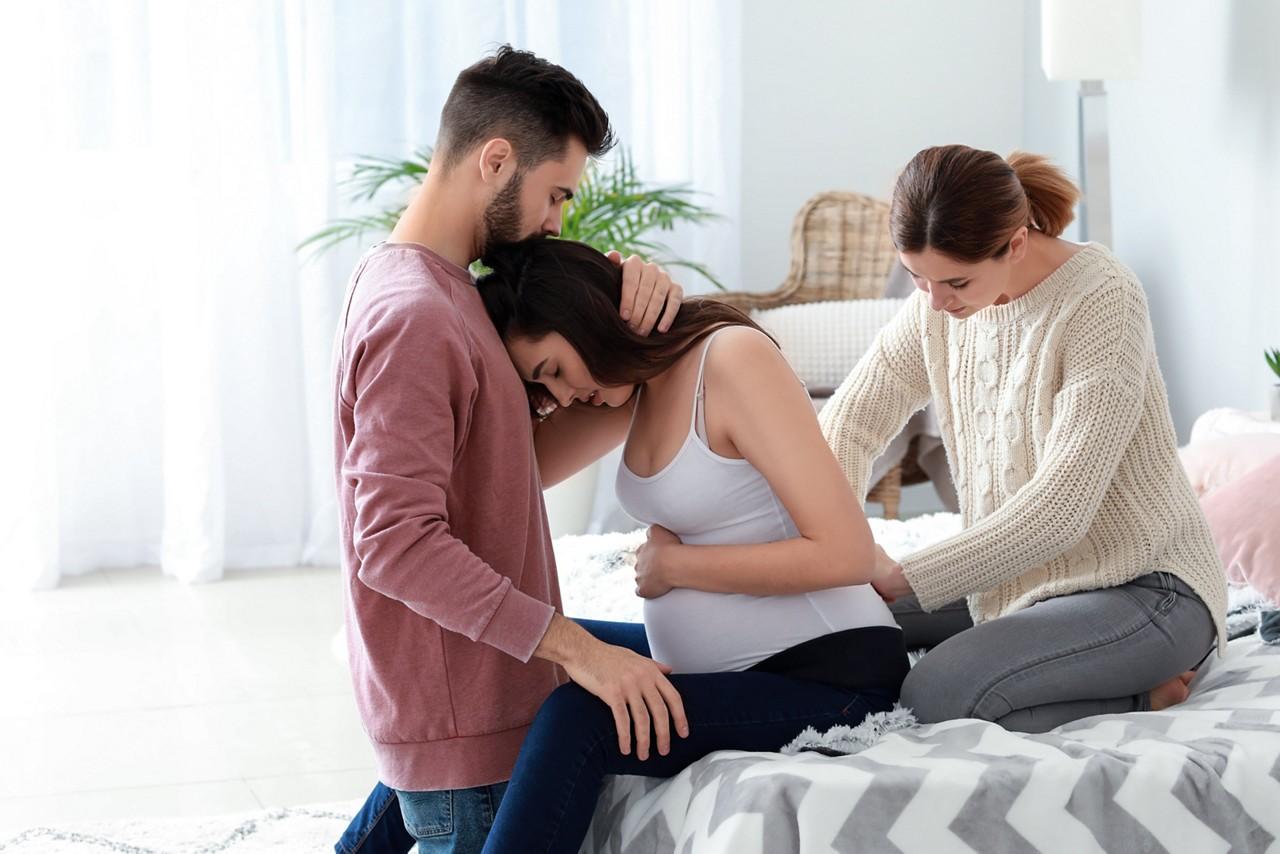 Hebamme massiert Kreuzbein der Schwangeren