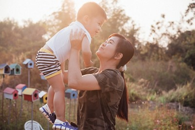Happy young mother playing and having fun with her little baby son in the park on a sunny summer day. Family on sunset