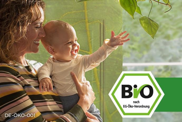 Bio Siegel Deutschland und Mama die glückliches Baby auf dem Arm hält