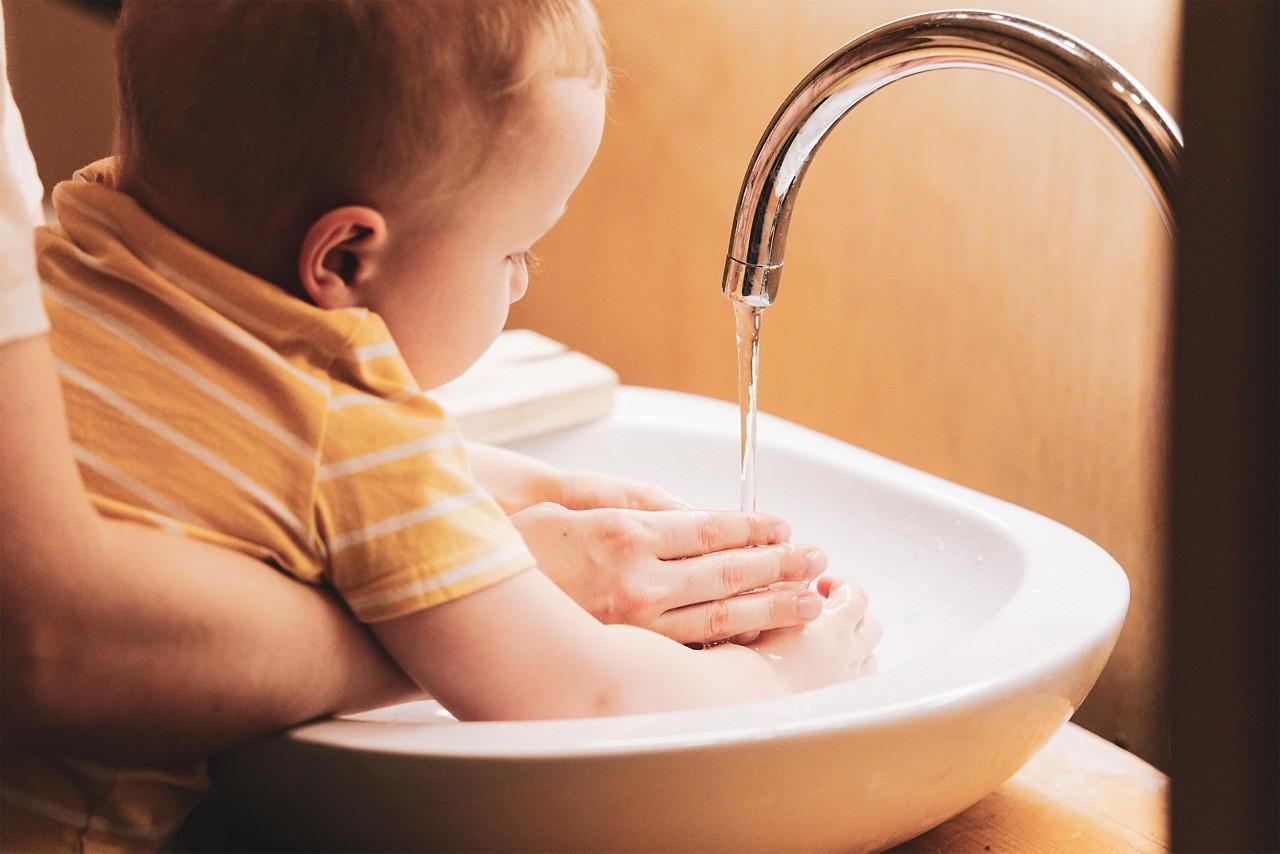 Babyhände unter Wasserstrahl