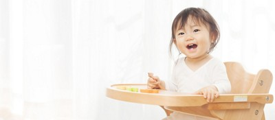 Smiling baby girl sitting on a baby high chair while holding a spoon