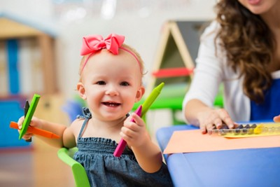 Smiling baby girl does colouring activity with wax crayons