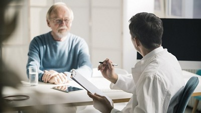 Doctor and clipboard with male patient during consultation