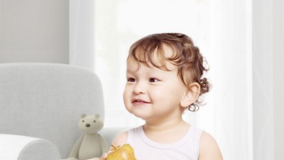 Cute baby girl with curly hair smiles and holds apple
