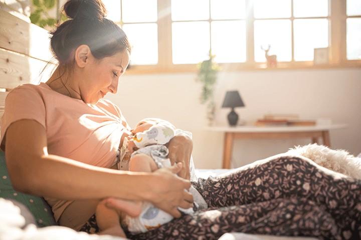 Mama hält Baby und Sonne scheint