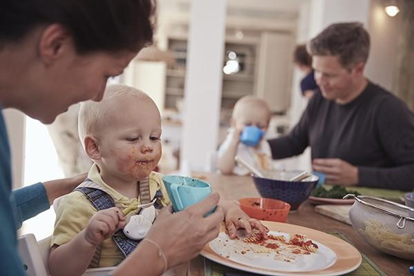 Kind isst Nudeln mit den Händen
