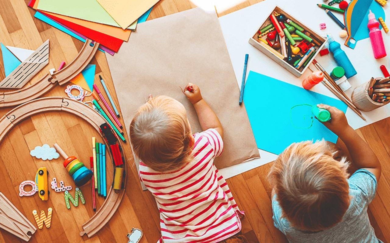 Kinder liegen auf Boden und malen