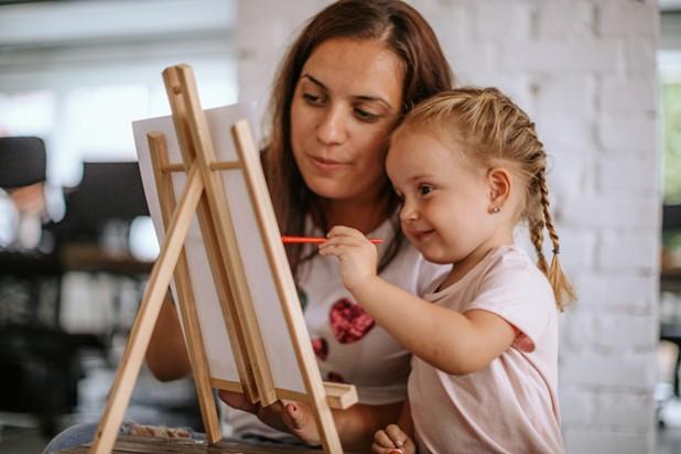 Kind mit Mama beim Malen auf einer Leinwand