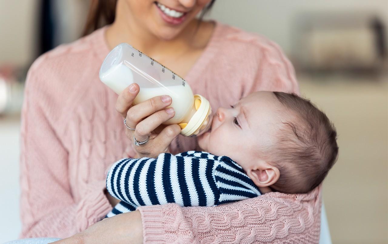 Mama füttert Baby mit Flasche.