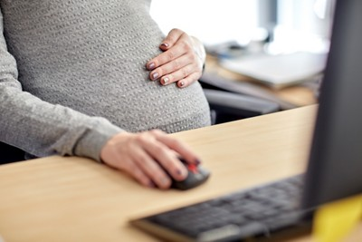 Pregnant businesswoman with computer at office