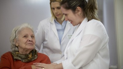 Two smiing doctors care for older woman sitting down