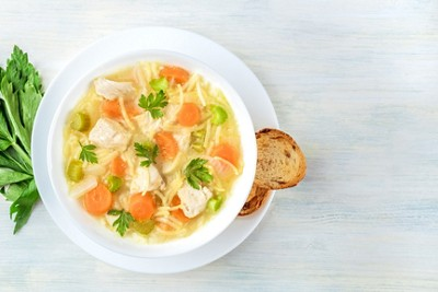 Chicken noodle soup shot from above with toasted bread and a place for text
