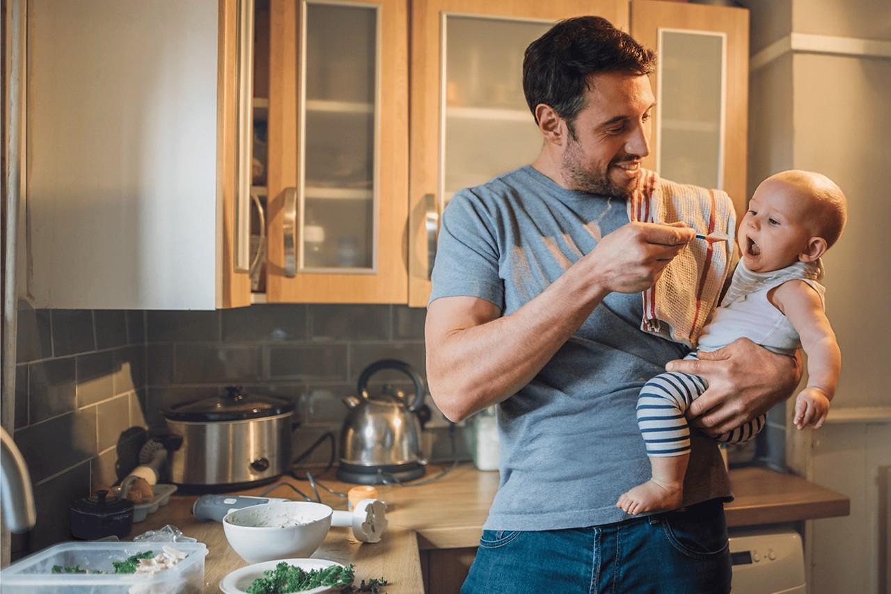 Vater füttern Baby auf seinem Arm einen Löffel Brei