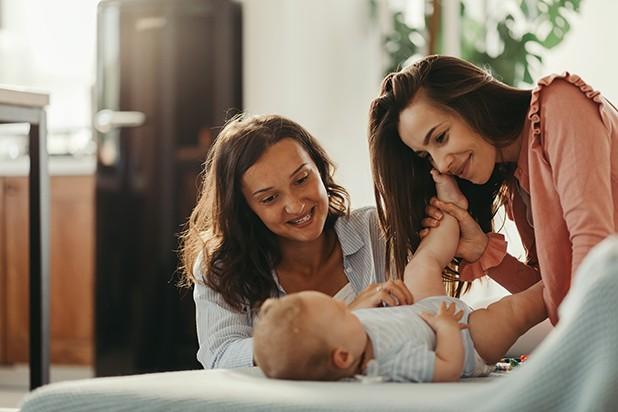 Zwei Frauen lächeln Baby an