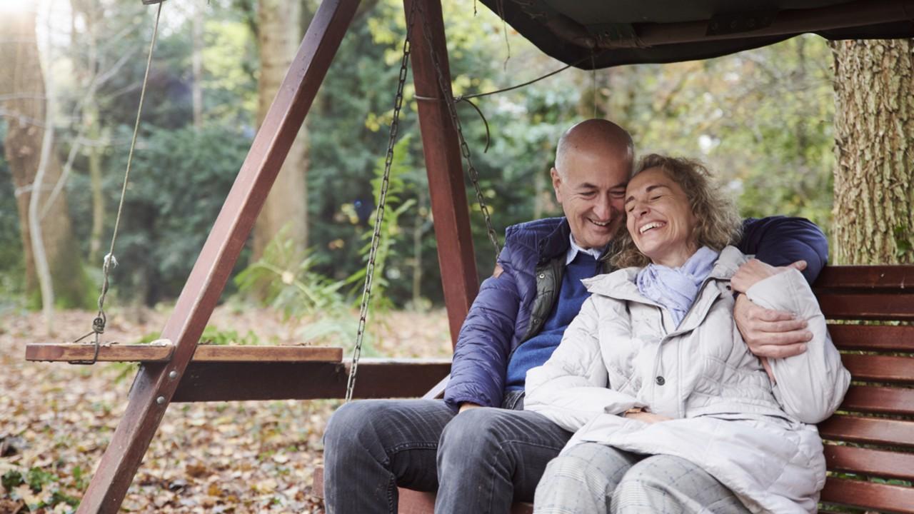 Elderly couple sitting on garden bench