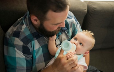Transition underlid leaflet father feeding baby with bottle at home